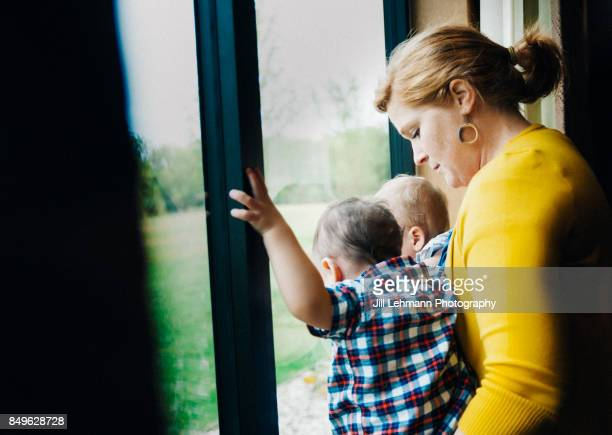 12 Month Old Fraternal Twins Are Assisted With Standing on a Window Sill