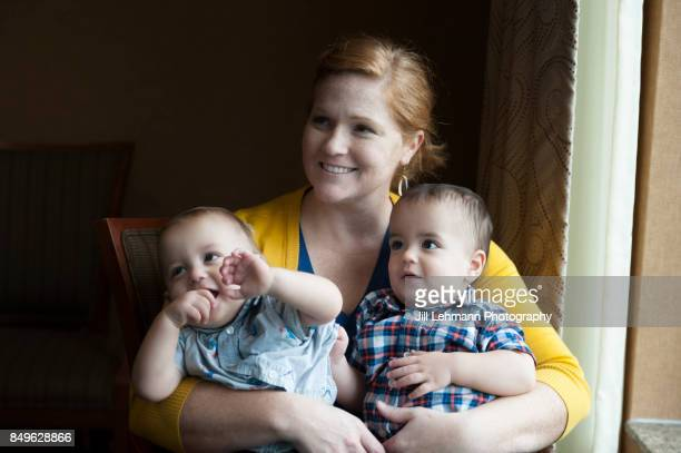 12 month old fraternal twins are embraced by mother - twin babies stock photos and pictures
