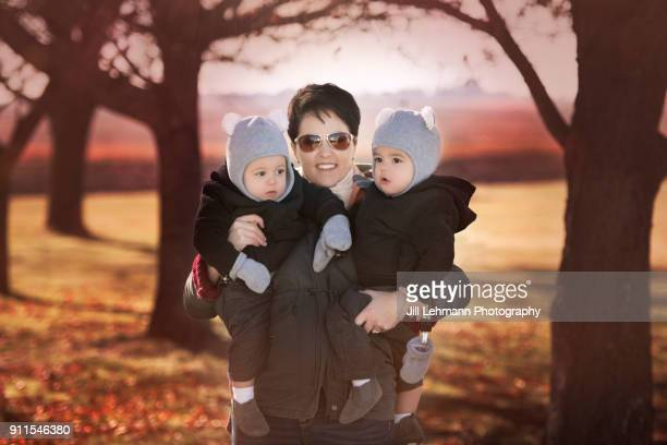 15 Month Old Fraternal Twins Are Held by Mother in the Autumn on a Farm in Iowa