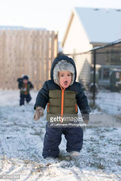 16 month old fraternal twins express excitement while walking in snow suits in the snow - enero fotografías e imágenes de stock