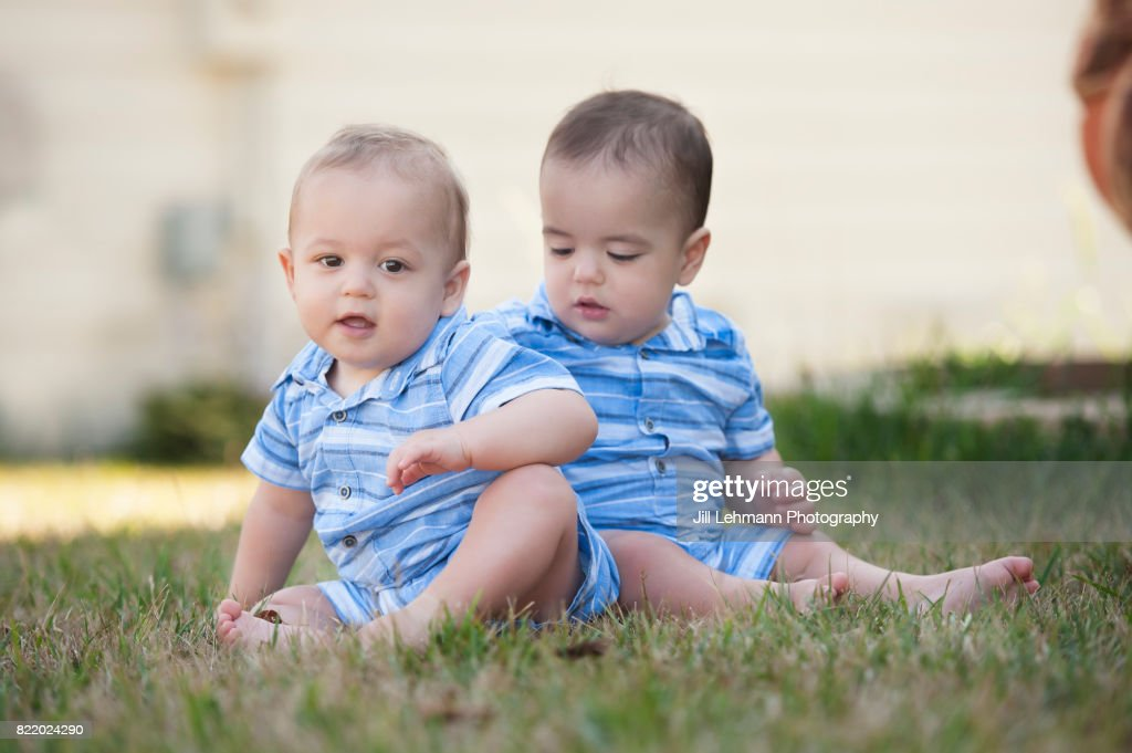 12 Month Old Fraternal Twins Sit on Grass at Home Together : Stock Photo