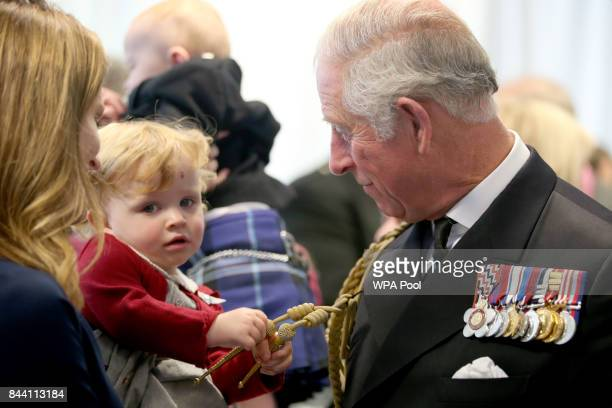 18 month old Imogen Holm pulls the braid on the uniform of Prince Charles Duke of Rothesay at a reception following the naming ceremony of aircraft...