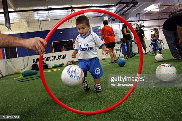 19 month old Kevin Madona kicks a ball through a hula hoop held by his father Steven Madona in a soccer class of 18 to 24 month old kids at South...