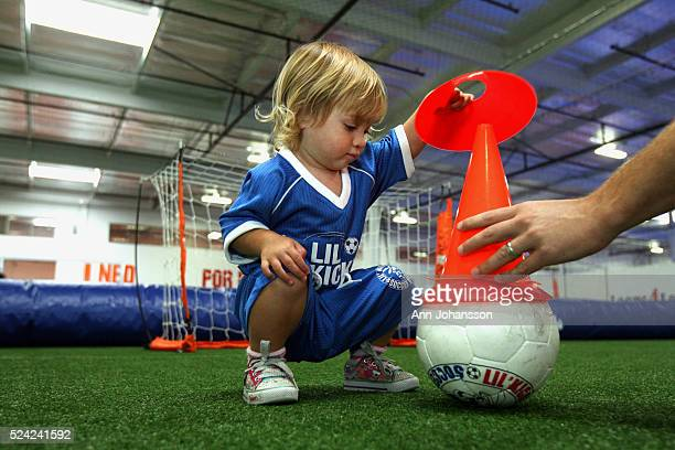 23 month old Kyli Scharmach is helped by her father Eric in stacking a soccer ball and a cone to be kicked down in a soccer class of 18 to 24 month...