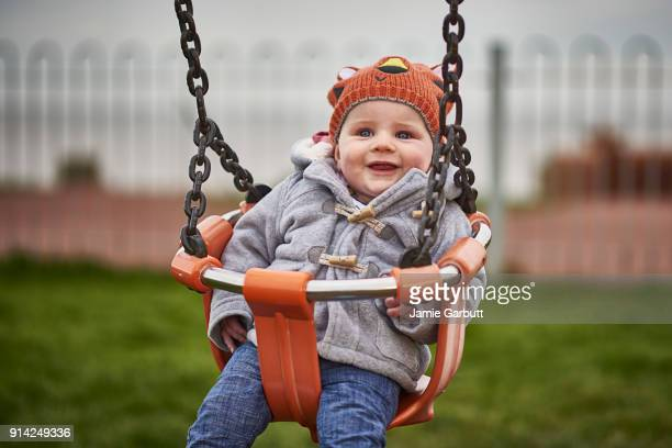 8 month old male British infant enjoying a swing