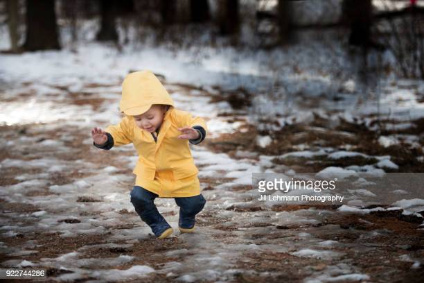 19 month old male toddler in yellow rain jacket falls on snow and ice in the woods - movimiento hacia abajo fotografías e imágenes de stock