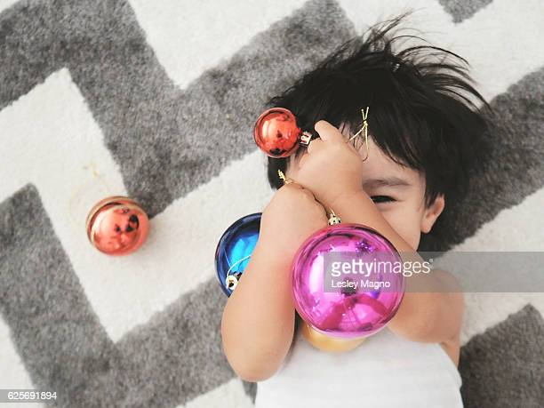 20 month old toddler is happily playing and hiding behind the Christmas balls