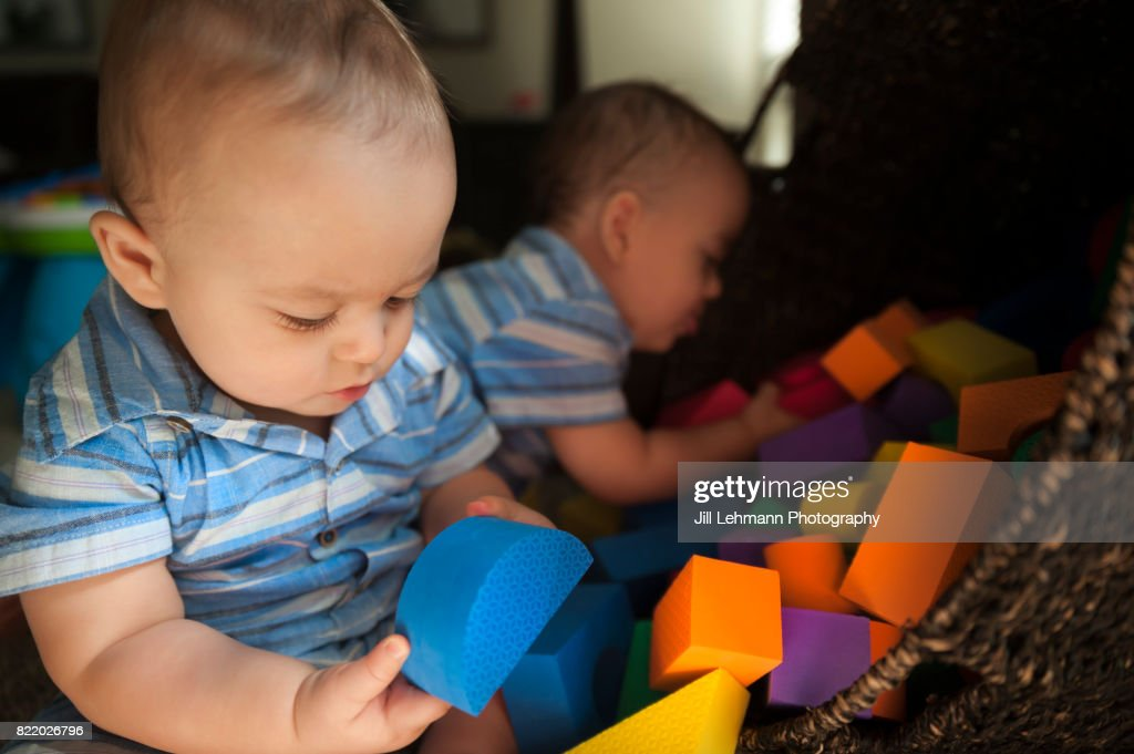 12 Month Old Twin Babies Spill and Play with Toy Blocks Together : Stock Photo