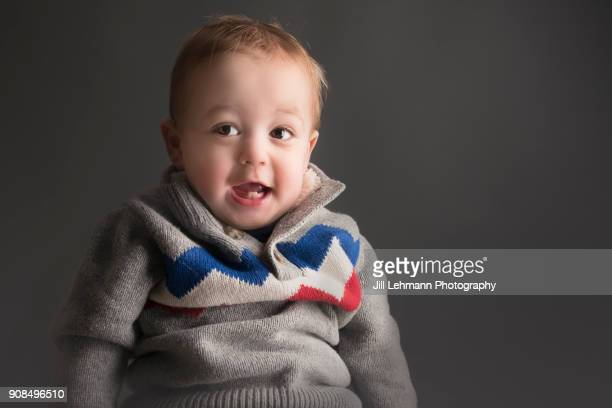 18 Month Toddler In Sweater Laughs While Sitting For a Portrait