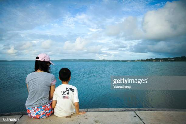 Monther and son looking the sky at the beach