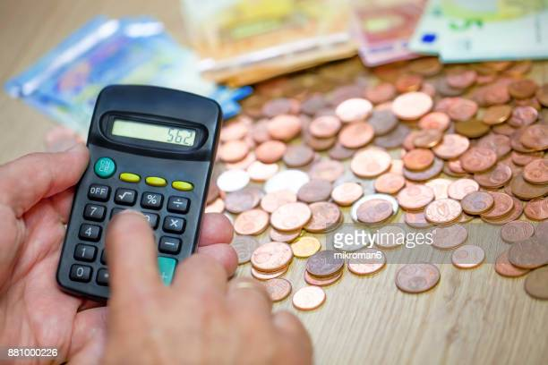 Monthly Expense Calculation- Close-up of man's hand using calculator to calculate expenses.