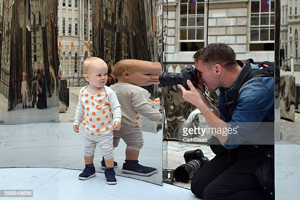 17 monthold Hugo Baumann Malcolmson is reflected as he is photographed exploring an installation entitled 'Bliss' created by Helidon Xhixha who is...