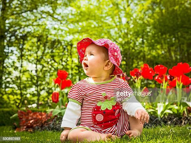 6-11 months, baby girl sitting in flower garden