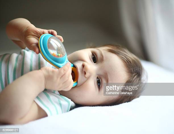 A 9 months old baby boy chewing a toy