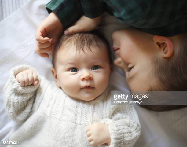 a 2 months old baby girl and her big brother - bébé stock photos and pictures