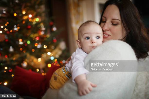 a 6 months old baby in the arms of his mum at home, in a christmas atmosphere - delahaye stock photos and pictures