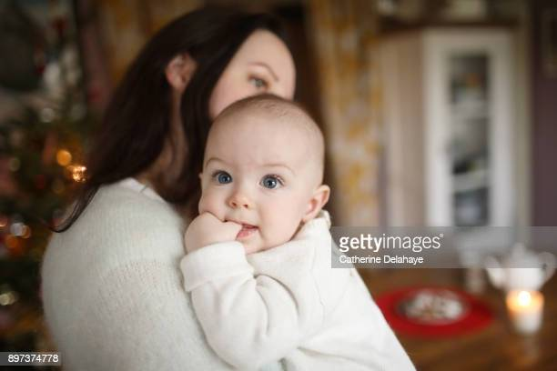A 6 months old baby in the arms of his mum at home, in a Christmas atmosphere