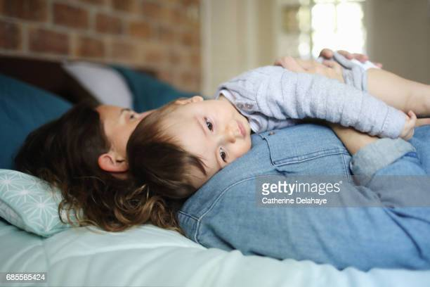 a 8 months old baby in the arms of his mum - delahaye stock photos and pictures