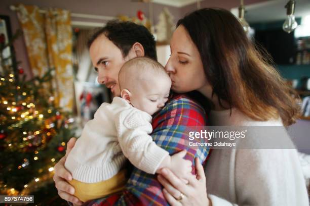 a 6 months old baby in the arms of his parents at home, in a christmas atmosphere - delahaye stock photos and pictures