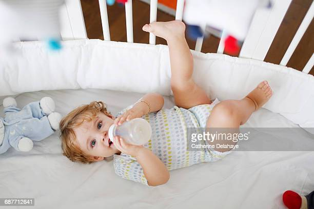 A 15 months old boy and a baby bottle in his crib