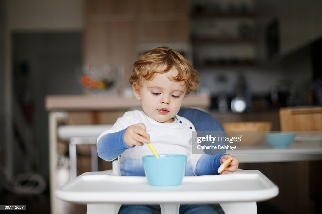 A 15 months old boy eating in his high chair : Stock Photo