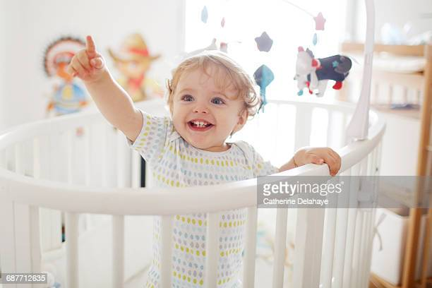 a 15 months old boy in his baby's crib - baby pointing stock photos and pictures