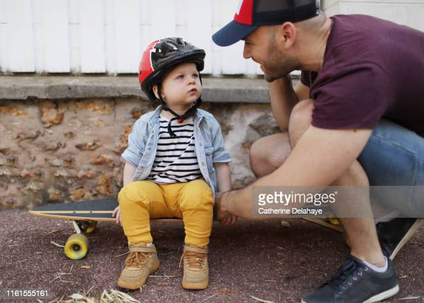 a 18 months old boy with his skateborder dad - 18 23 meses fotografías e imágenes de stock