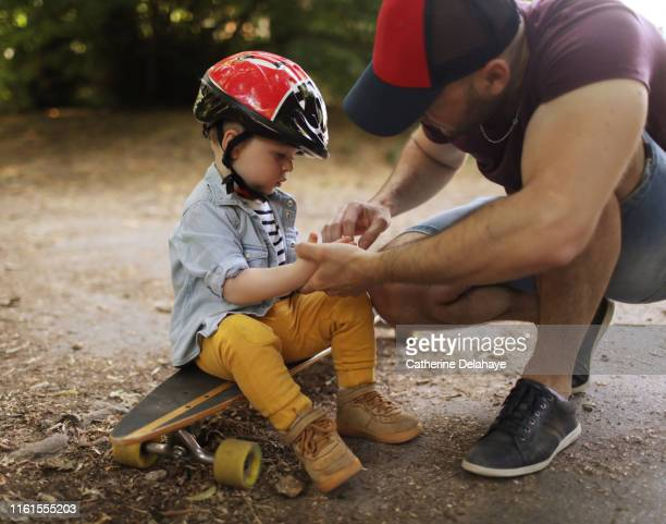 a 18 months old boy with his skateborder dad - work helmet stock pictures, royalty-free photos & images