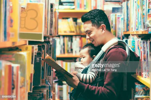 9 months old Chinese baby boy reading book joyfully with father in bookstore