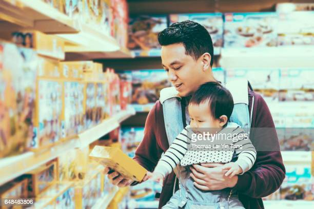 9 months old chinese baby boy visiting toy store with daddy joyfully
