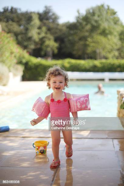 A 18 months old girl with water wings by the swimming pool