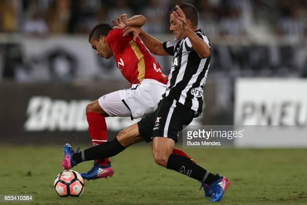 Montillo of Botafogo struggles for the ball with Lucas Rodrguez of Estudiantes during a match between Botafogo and Estudiantes as part of Copa...