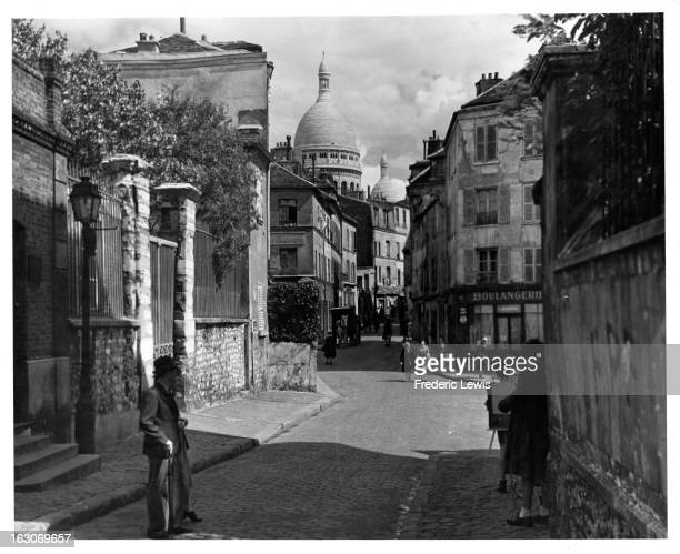 Montmartre district primarily known for the whitedomed Basilica of the Sacré Cœur in the background in Paris France 1955