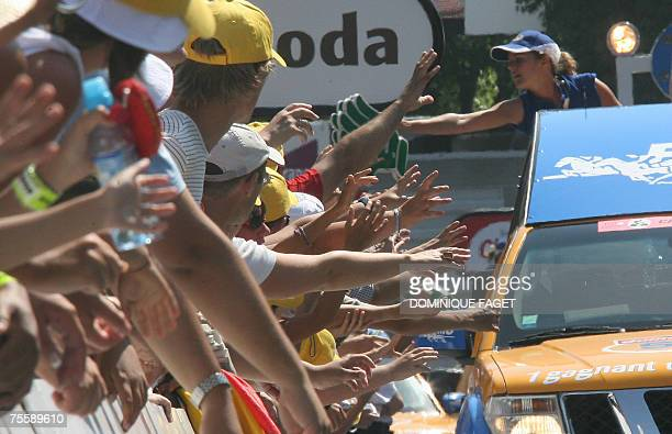 Spectators grab samples as the advertising caravan rides by during the 11th stage of the 94th Tour de France cycling race between Marseille and...