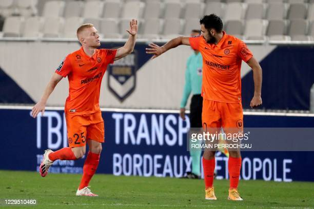 Montpellier' French midfielder Florent Mollet celebrates with a team mate after he scored a goal during the French L1 foobtall match between Bordeaux...