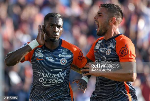 Montpellier's Cameroon midfielder Ambroise Oyongo reacts after scoring next to Montpellier's French forward Andy Delort during the French L1 football...