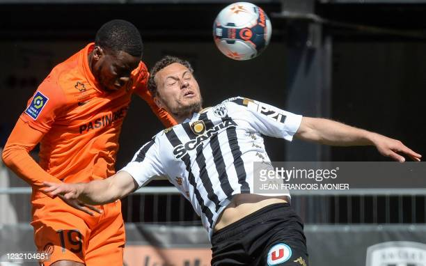 Montpellier's English forward Stephy Mavididi headers the ball and score despite Angers' French defender Vincent Manceau during the French L1...