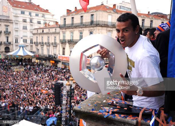 Montpellier's football club Brazilian defender Victorino Hilton holds the trophy as he celebrates with his teammates and supporters at the place de...