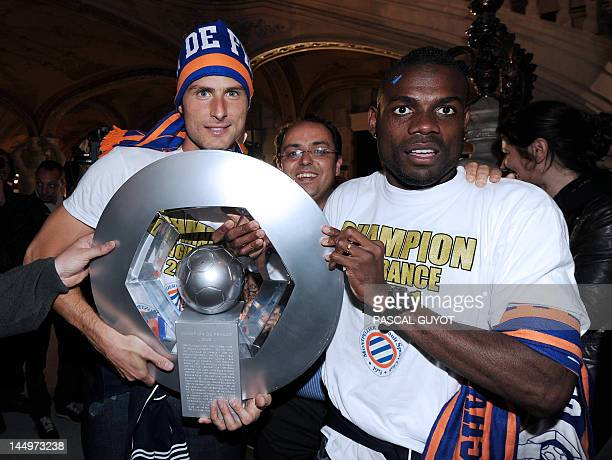 Montpellier's football club defender Henri Bedimo and striker Olivier Giroud hold the trophy as they celebrate with supporters at the place de la...