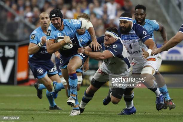 Montpellier's French centre Alexandre Dumoulin runs to evade Castres' French prop Antoine Tichit during the French Top 14 final rugby union match...