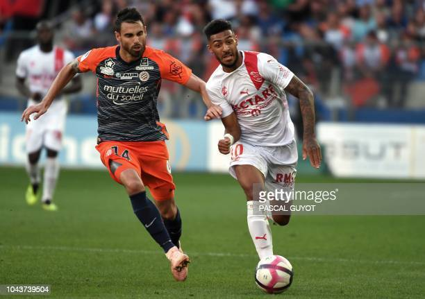 Montpellier's French defender Damien Le Tallec vies with Nimes' French midfielder Denis Bouanga during the French L1 football match between...