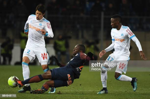 Montpellier's French defender Jerome Roussillon vies with Marseille's French forward Bouna Sarr and Marseille's Japanese defender Hiroki Sakai during...