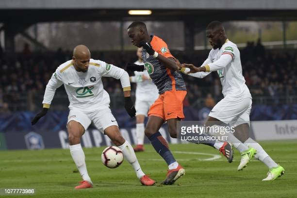 Montpellier's French defender Junior Sambia vies for the ball with Entente SSG's French defender Jeremy Labor and Entente SSG's Senegalese midfielder...