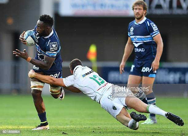 Montpellier's French flanker Fulgence Ouedraogo is tackled by Pau's New Zealander fullback Tom Taylor during the French Top 14 rugby union match...