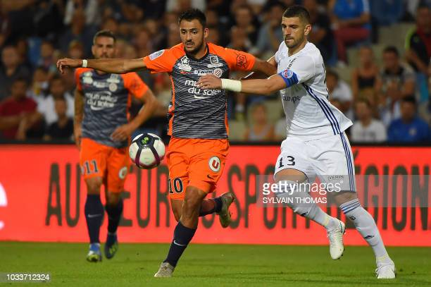 Montpellier's French forward Gaetan Laborde vies with Strasbourg's defender Stefan Mitrovic during the French L1 football match between Montpellier...