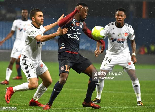 Montpellier's French forward Isaac Mbenza vies with Amien's SouthAfrican midfielder Bongani Zungu and Amiens' Moroccan defender Oualid ElHajjam...