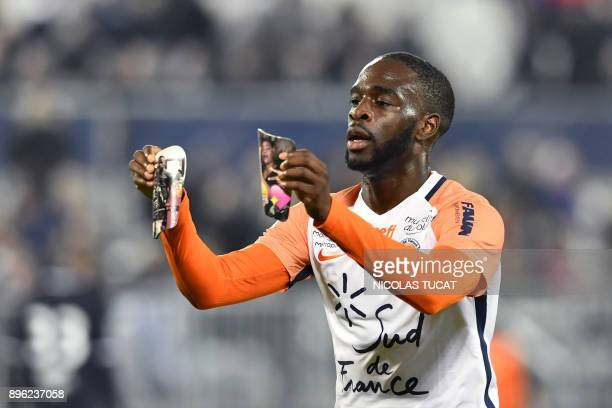 Montpellier's French forward Jonathan Ikone holds pictures as he celebrates scoring a goal during the French L1 football match between Bordeaux and...