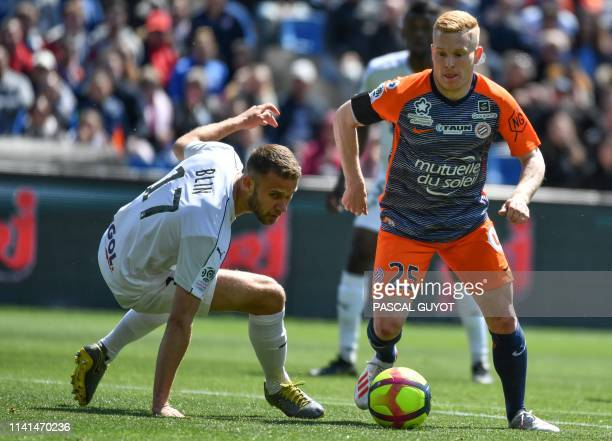 Montpellier's French midfielder Florent Mollet fights for the ball with Amiens' French midfielder Alexis Blin during the French L1 football match...