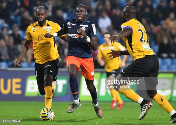 Montpellier's French midfielder Junior Sambia fights for the ball with Nancy's French defender Herve Lybohy and Nancy's Guinean defender Ernest Seka...