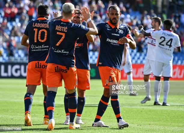 Montpellier's players celebrate after a team goal during the French L1 football match between Montpellier and Nice at the Mosson Stadium in...